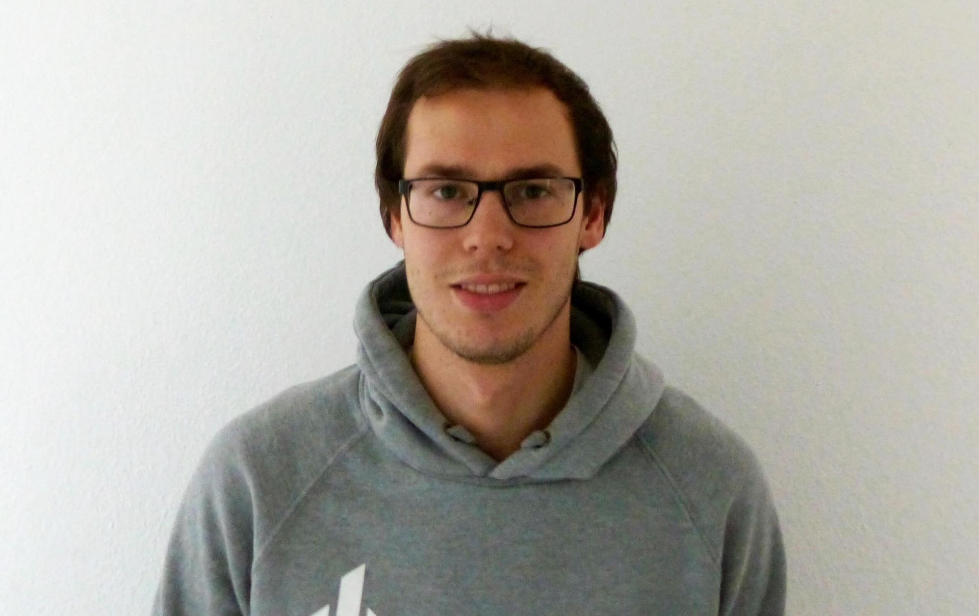 Stefan Asche steht vor weißer Wand